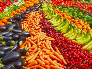 beautiful vibrant product: eggplants, carrots, strawberries, bananas and more laid out.