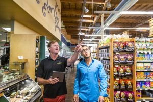 two men in a grocery store pointing at lights